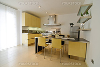 Modern kitchen interior with yellow cabinets and gray table