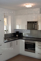 bright modern kitchen with stainless steel appliances and white decors