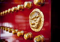 A brass-painted lion door handle on a red gate in an Oriental palace.