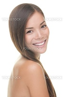 Natural beauty woman smiling. Beauty portrait of brunette with perfect natural fresh look and skin. Isolated on white background. Mixed Caucasian / Asian female model.
