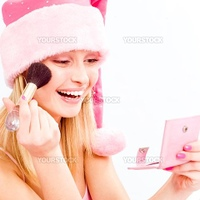 Santa helper putting on make-up and smiling