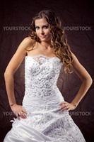 Fashion model wearing wedding dress at brown studio background
