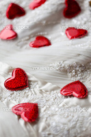 Wedding or valentine background as sparse red hearts on white ornate textile