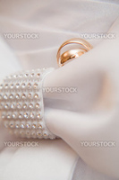 Wedding rings on detail of bridal dress