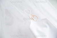 Two golden wedding rings and mitt on white veil