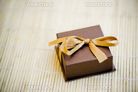 Gift in small brown box with golden bow