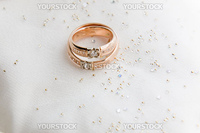 Two gold wedding rings on white textile background closeup, horizontal image.