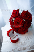 Wedding rings in box and bridal bouquet from red roses