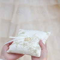Wedding ring on silk cushion in kids's hands
