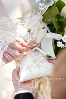 Bride taking ring from silk cushion at wedding ceremony