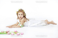 Adorable child lying on white background near tulips