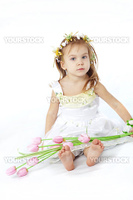 Little girl in spring flower dress isolated on white background with tulips