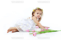 Beautiful little girl in dress lying near tulips on white background