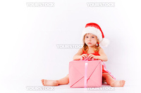 Sad little Santa girl sitting with present box on white studio background