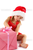 Little Santa girl unpacking gift box on white background