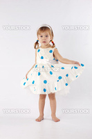 Sweet little girl wearing beautiful dress posing in studio