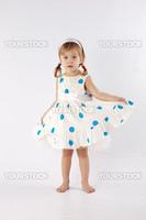 Sweet little girl wearing beautiful dress posing in studio