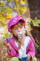 Funny child blowing soap bubbles in autumn park