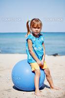 Child sitting in big gymnastic ball on beach