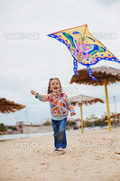 Cute child flying a kite outdoors