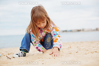 Cute child playing with sand at beach