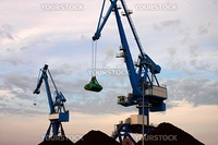 Blue cranes on the port with sunset and sand