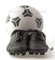 Soccer ball with two old black soccer shoes, isolated over white