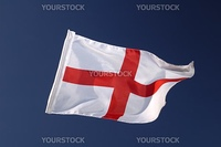The cross of St George, the flag of England, isolated against a clear blue sky. Motion blur at the tip of the flag.