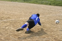 Football goalkeeper falling down on the ground to catch the ball.