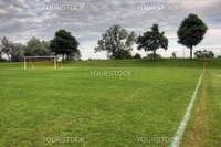 A cloudy unoccupied soccer field with trees in the background. (HDR photograph)