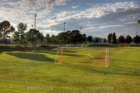 A mixed sky over an unoccupied soccer field with trees in the background. (HDR photo)