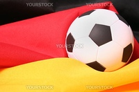 The flag of Germany and a football symbolizing the german national soccer team.