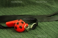A red whistle with a soccer ball print placed on a green grass surface