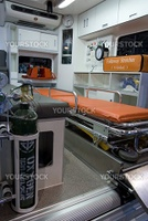 Interior of ambulance vehicle with stretcher and emergency equipment. Oxygen bottle in the foreground.