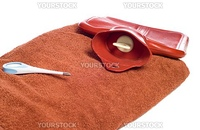 Three objects people commonly use when they are sick, including a hot water bottle, a thermometer, and a towel, isolated against a white background