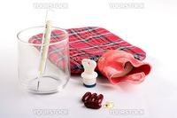Medical hot-water bottle with a stopper and a thermometer for temperature measurement in a glass.