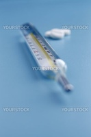Isolated thermometer and pills - abstract medical background.