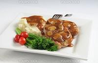 Pork chops potatoes and vegetables with mushroom gravy.