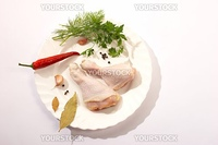 fresh chicken's legs and red pepper wih parsley on the plate