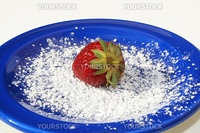 Single strawberry on blue plate with powdered sugar