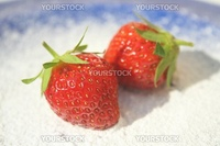 Two ripe red strawberries on blue plate and powdered sugar under them