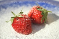 Two ripe red strawberries on blue plate with powered sugar sprinkled on them