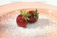 Two strawberries on powdered sugar on pink glass plate