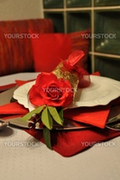 Richly decorated dinner plate with rose and golden decoration. Tiled stove and cozy corner seat in the background.