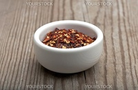 Crushed Chillies In A White Dish, On A Wooden Kitchen Table