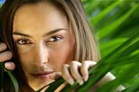 Portrait of a woman behind a palm leaf