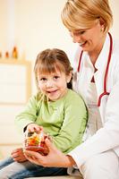 Kinderarztin gibt kleiner Patientin Gumm
