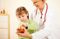 Kinderarztin gibt Patientin Gummibarchen