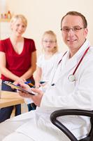 Kinderarzt mit Familie in seiner Praxis