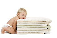 Baby girl resting head on pile of towels